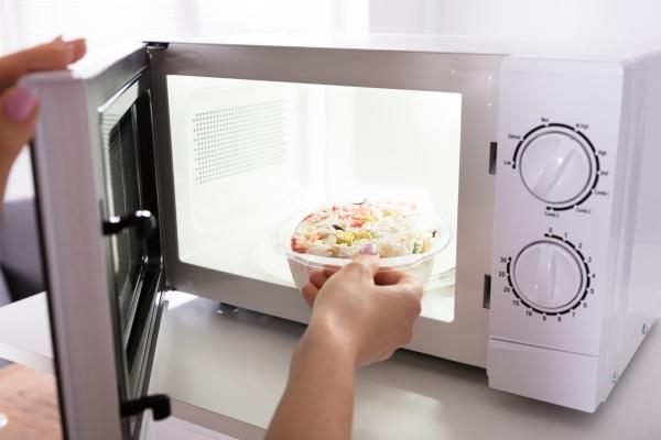donna riscaldamento cibo in forno a
