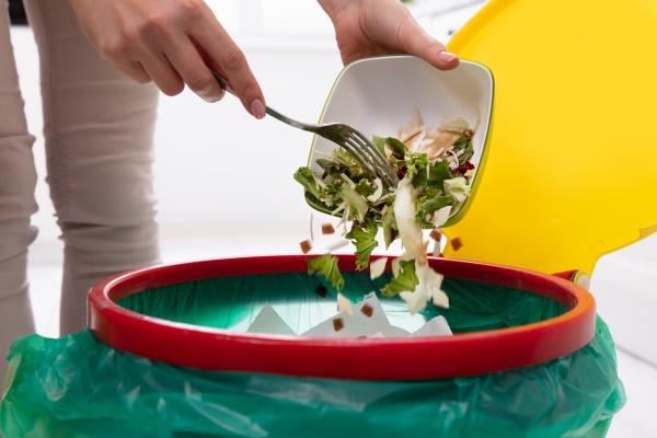 donna gettando verdure nel cestino