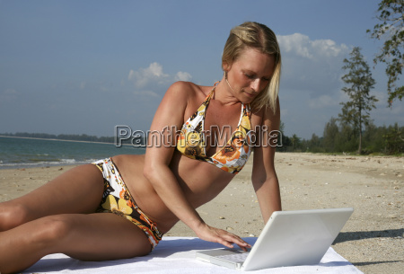 woman with laptop on the beach