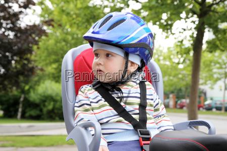 bambino seduto in bicicletta in casco