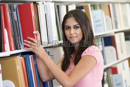 donna in libreria libro tirando fuori
