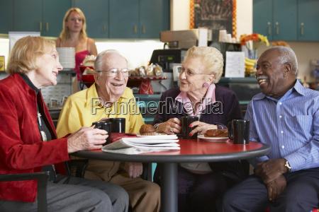 adulti senior che mangiano insieme il