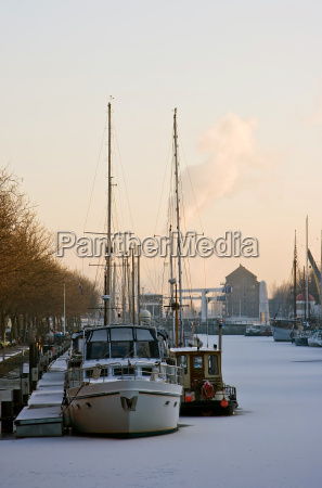 frozen harbour with ships in winter