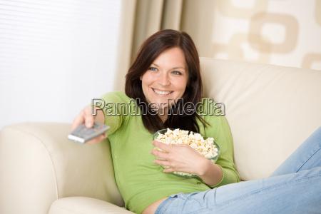 donna guardando la televisione con popcorn