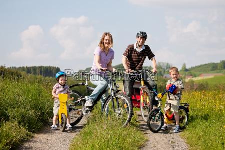 famiglia cavalca una bici in estate