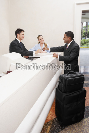 uomo daffari e due receptionist ad