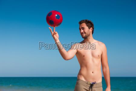man on the beach balances football