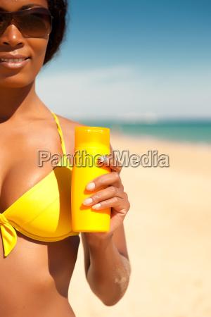 woman on beach with sunscreen