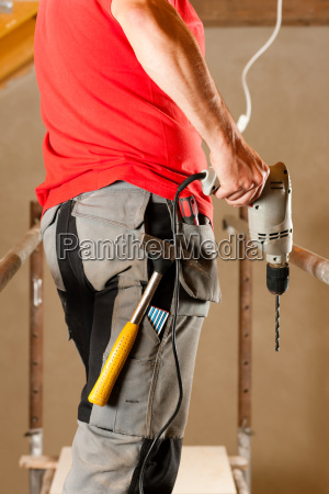 construction worker or handyman with bohrmasc