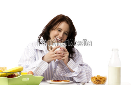 young laughing woman eating breakfast