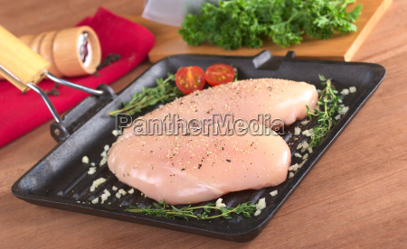 raw chicken breast in frying pan
