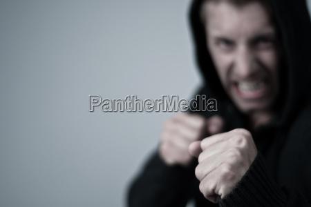 giovane aggressivo in posizione di pugilato