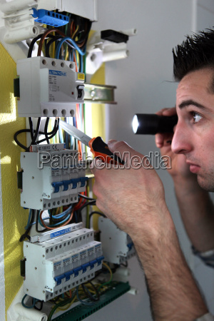 elettricista che esamina un fusebox con