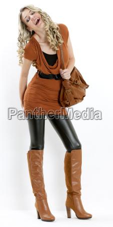 donna in piedi indossando stivali marroni