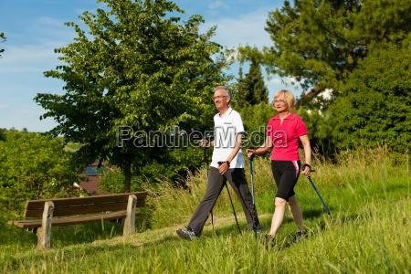 felice coppia di anziani nordic walking