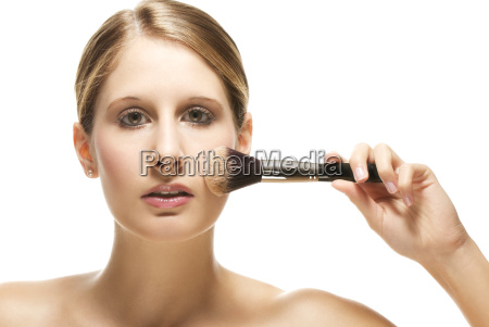 young woman is applying make up