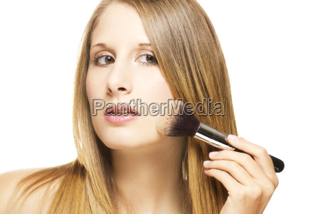 young woman with brush puts on