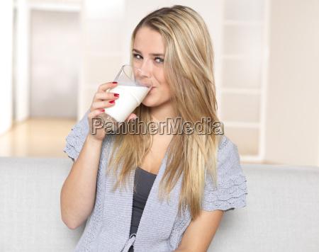 giovane donna beve bicchiere di latte