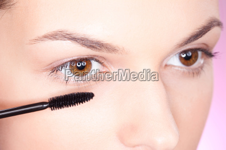bella donna applicando mascara su occhio