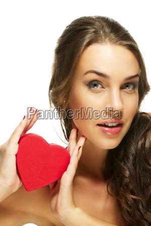 beautiful brunette woman showing red heart