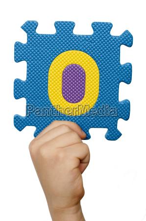 children hand holding the number zero