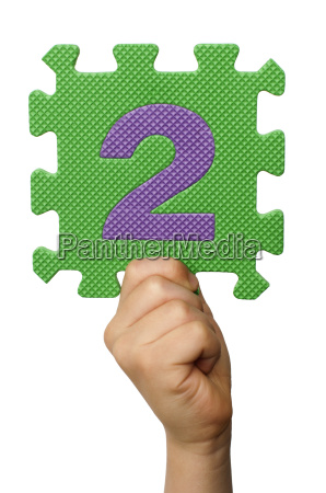 children hand holding the number two