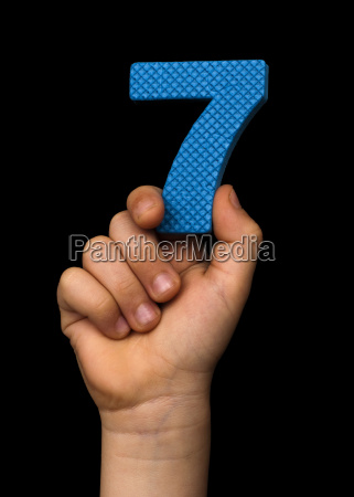 children hand holding the number seven