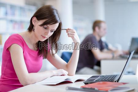 studentessa con laptop e libri lavorando