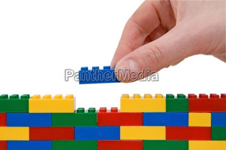 mano che costruisce lego