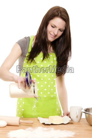 young woman pours flour on the