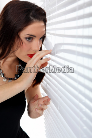 donna che scruta attraverso le veneziane
