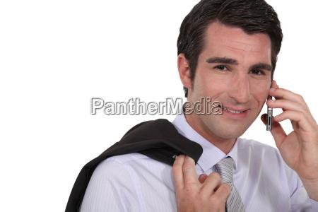 businessman stood with jacket over shoulder