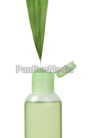 green cosmetic bottle and leaf