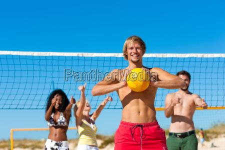 friends play beach volleyball
