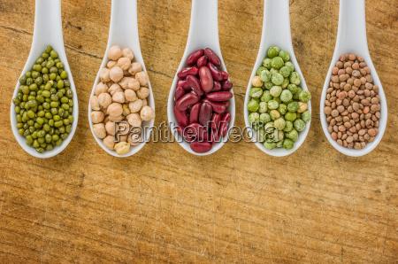 vari legumi in cucchiai di porcellana