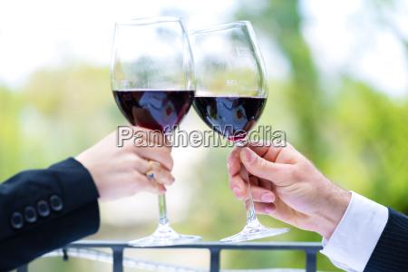 mani che tengono bicchieri di vino
