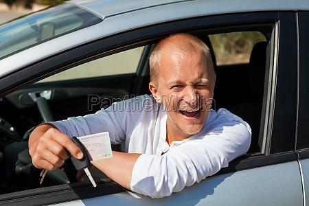 giovane adulto in macchina nuova con