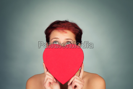 young woman behind red heart looks
