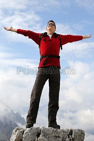 giovane alpinista in vetta tema di