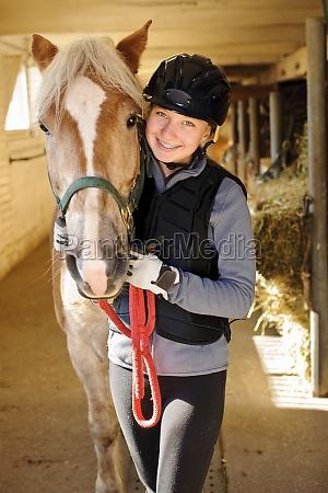 cavaliere con cavallo in stalla