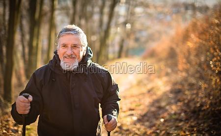 uomo anziano nordic walking godersi la