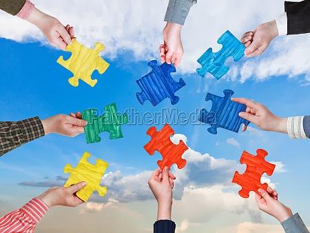 persone mani con pezzi di puzzle
