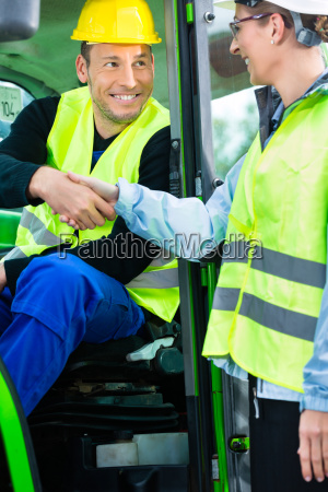 construction worker shaking construction managers hand