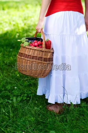 young woman holding basket filled fresh