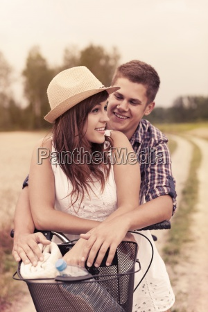 young couple having fun on bicycle