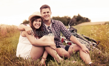 couple resting on grass after biking