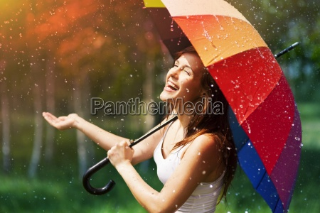 laughing woman with umbrella checking for