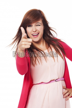 cheerful young woman pointing at camera