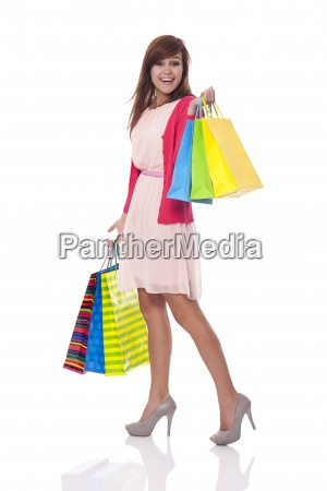 smiling young woman carrying many shopping