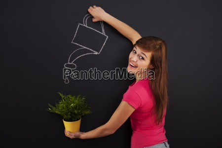 smiling woman watering flower
